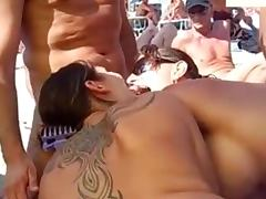 Two girls suck a cock on a beach and get cum on their tits