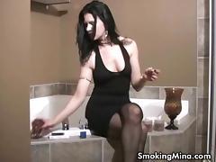 Brunette babe smoking while soaking into the bathtub